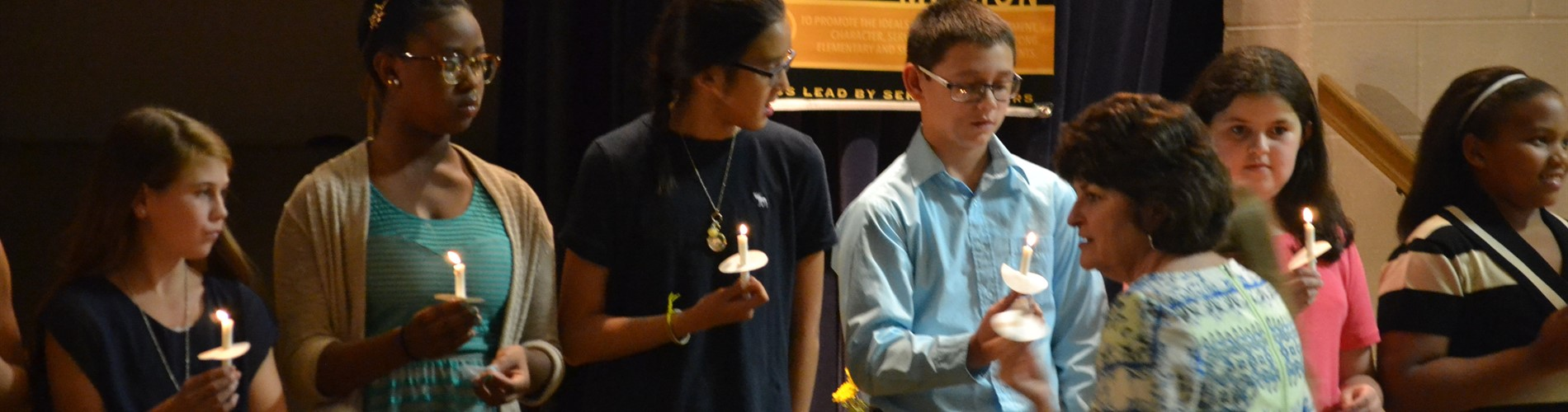 Students holding candles during Jr Beta ceremony