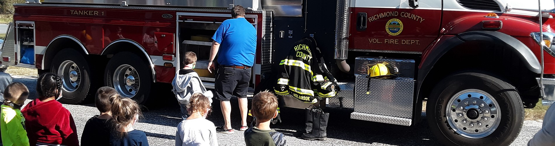Mackey Thompson Learning Center students standing in front of a fire truck.