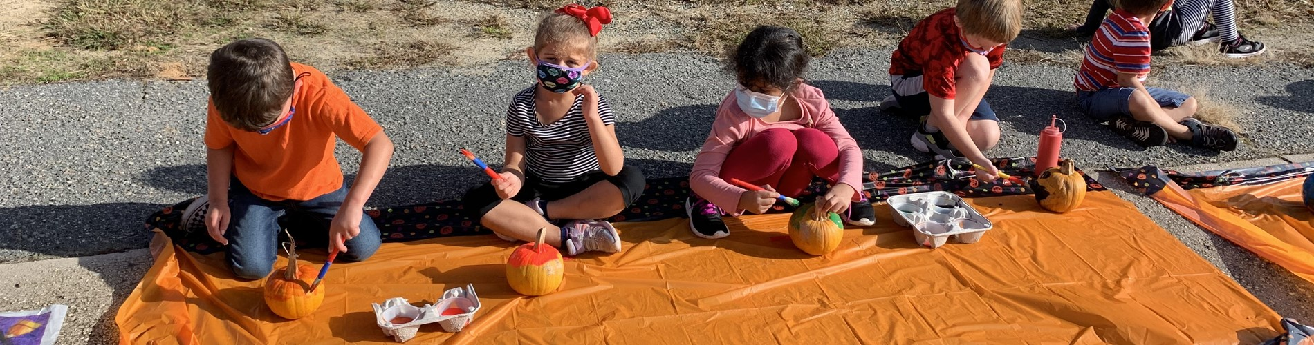 Mackey-Thompson students painting small pumpkins on the pavement with an orange plastic tablecloth underneath them.