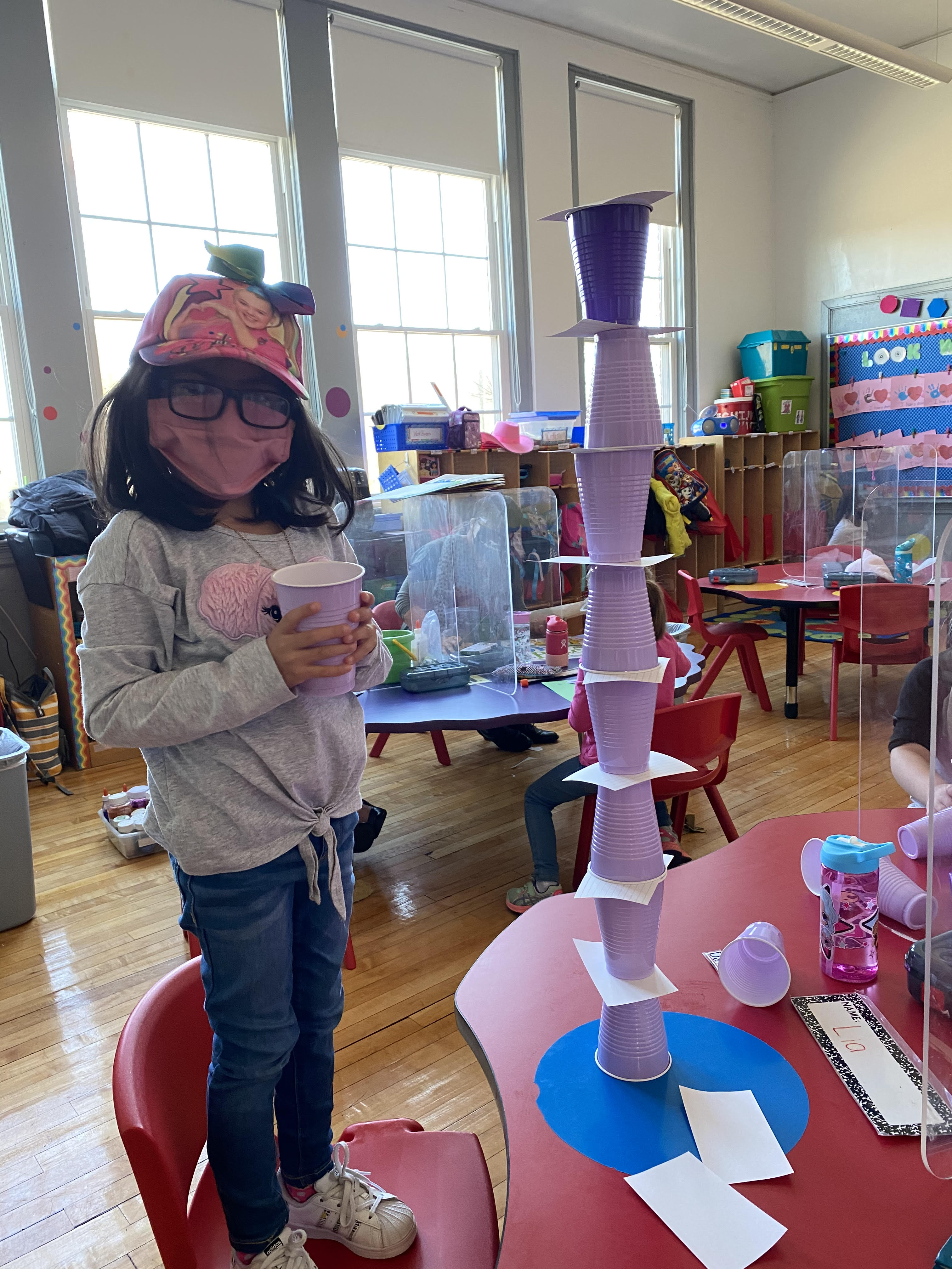 Student standing beside pink and purple stacked plastic cups.